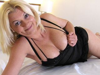 Blonde mature tramp playing with herself on the couch